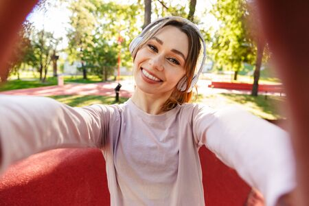Image of a beautiful cheerful young fitness sports woman posing outdoors in park listening music with earphones take selfie by camera.