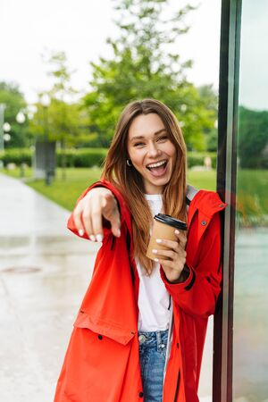 Cheerful attractive young girl wearing raincoat spending lovely time outdoors, drinking takeaway coffee