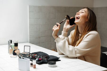 Beautiful young woman doing her makeup at the kitchen, talking on mobile phone Фото со стока