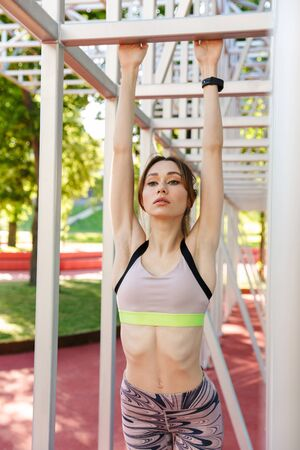 Image of a beautiful young fitness sports woman posing outdoors in park make exercises.