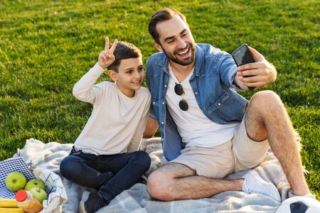 Happy young father having a picnic with his little son at the park, taking a selfie