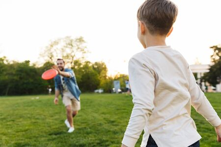 Image of a happy young man having fun with his little brother or son outoors in park beautiful green grass play game.