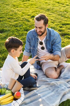 Happy young father having a picnic with his little son at the park, playing