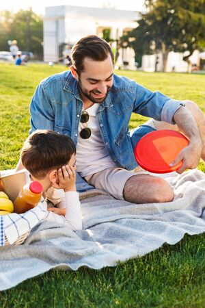 Two happy brothers spending fun time at the park, having a picnic on grass