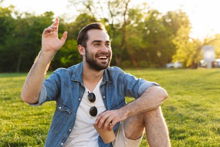 Cheerful young man having a picnic at the park, holding cup, waving