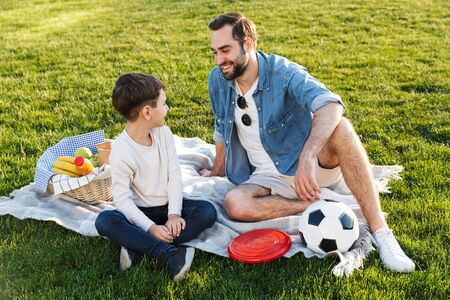 Two happy brothers spending fun time at the park, having a picnic on grass 写真素材 - 128692867