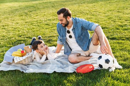 Two happy brothers spending fun time at the park, having a picnic on grass 写真素材 - 128693049
