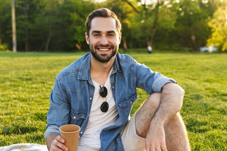 Cheerful young man having a picnic at the park, holding cup Imagens