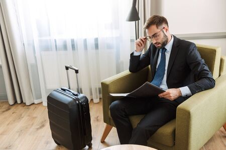 Attractive confident young businessman wearing suit sitting in a chair at the hotel room, working with documents Stock Photo