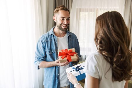 Beautiful young couple in love at home, celebrating with a gift box exchange 版權商用圖片