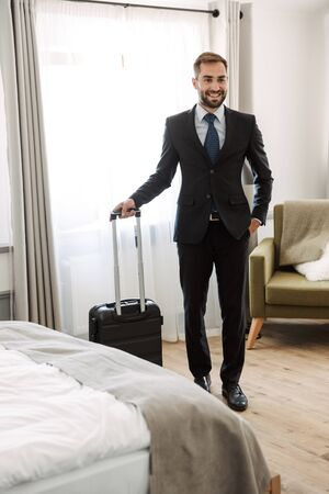 Attractive young businessman wearing suit standing at the hotel room, carrying suitcase,just arrived