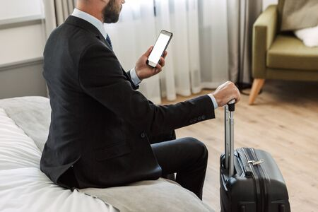 Cropped image of a young businessman wearing suit sitting at the hotel room, using blank screen mobile phone while carrying suitcase
