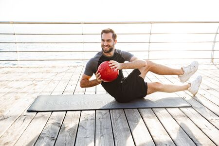 Smiling young sportsman working out on a fitness mat at the beach, using medicine ball Banco de Imagens