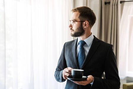 Attractive young businessman wearing suit standing at the hotel room, holding cup of coffee Stock Photo