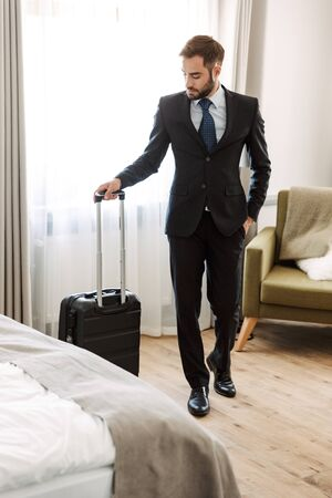 Attractive young businessman wearing suit standing at the hotel room, carrying suitcase,just arrived Banco de Imagens