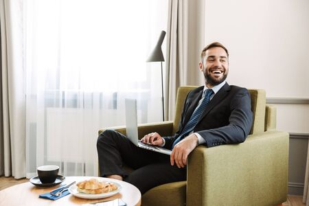 Attractive young businessman wearing suit sitting in a chair at the hotel room, working on laptop computer while having breakfast Stockfoto