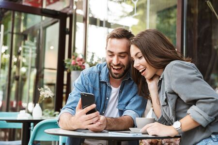 Attractive young couple in love having lunch while sitting at the cafe table outdoors, using mobile phone