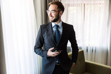 Attraente giovane uomo d'affari sorridente che indossa un abito in piedi nella camera d'albergo, utilizzando il telefono cellulare Archivio Fotografico