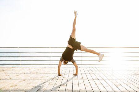 腕の手の上に立っている海の近くのビーチでハンサムな強い若いスポーツマンの写真は、ヨガのカートホイールの練習を行います。