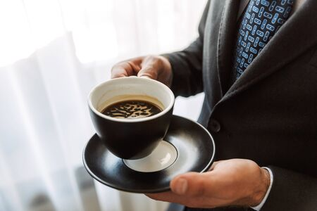 Close up of a young businessman wearing suit standing at the hotel room, holding cup of coffee
