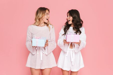 Image of excited happy young two pretty women girls friends sisters posing isolated over pink wall background holding present boxes.