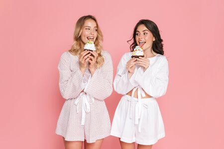 Image of excited young pretty women friends posing isolated over pink wall background drinking cocktails.
