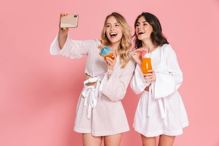 Image of excited happy young pretty women friends posing isolated over pink wall background drinking cocktails take a selfie by phone. Standard-Bild