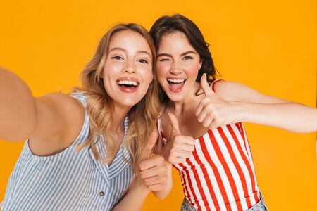 Portrait closeup of two joyous blonde and brunette women 20s in summer wear smiling while looking at camera isolated over yellow background