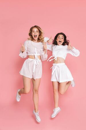 Image of a young cheery emotional happy friends women jumping isolated over pink wall background with mouth opened showing thumbs up. 写真素材