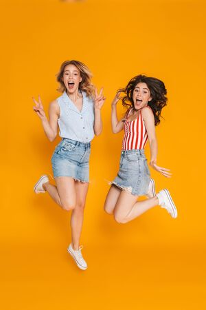 Portrait of two amazed blonde and brunette women 20s in denim skirts gesturing peace sing and jumping isolated over yellow background