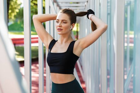 Photo of brunette young woman 20s wearing tracksuit doing workout with horizontal metal bar on sports ground in green park Stock fotó