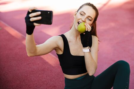 Photo of cute young woman 20s wearing tracksuit taking selfie on smartphone and eating apple while sitting on sports ground during workout in green park Foto de archivo