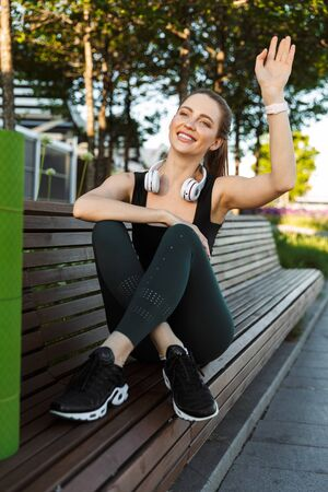 Image of young sportswoman 20s wearing tracksuit waving hand while sitting on bench with fitness mat in city park Foto de archivo
