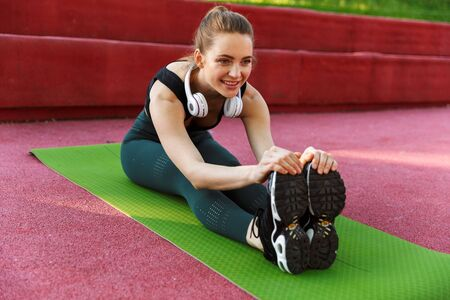 Photo of lovely sporty woman 20s wearing tracksuit smiling and stretching her body on fitness mat during workout in green park 写真素材