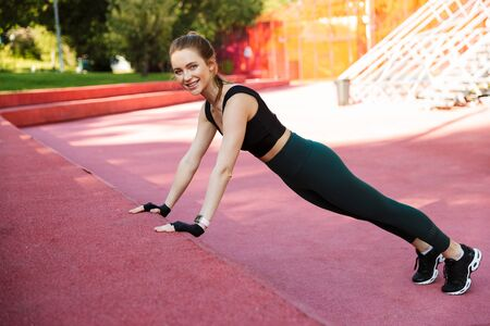 Photo of brunette young woman 20s wearing tracksuit smiling and doing push-ups during workout on sports ground