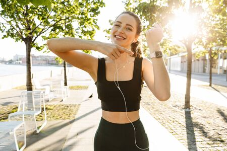 Image of beautiful sportswoman 20s wearing tracksuit listening to music with earphones and pointing at her wristwatch during workout in city park 写真素材