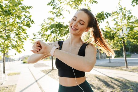 Image of brunette sportswoman 20s wearing tracksuit listening to music with earphones and looking at her wristwatch during workout in city park