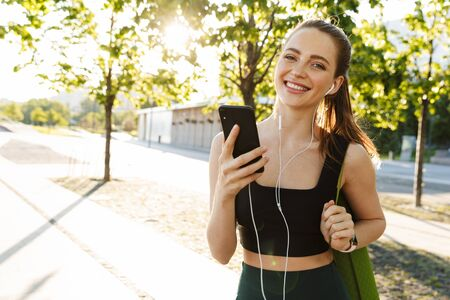 Image of feminine sportswoman 20s wearing tracksuit holding smartphone and listening to music with earphones during walk through city park 写真素材