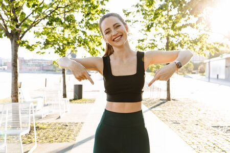 Image of athletic sportswoman 20s wearing tracksuit smiling and pointing fingers at her abs belly during workout in city park