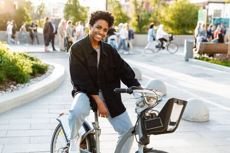 Photo of young african american woman wearing casual clothes smiling while sitting on bicycle in city park