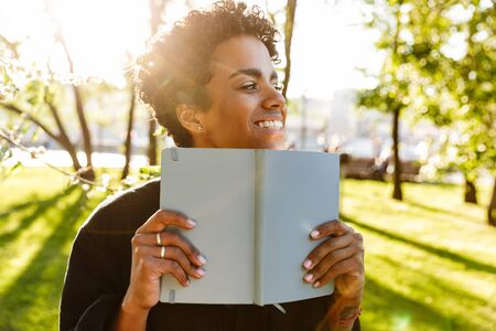 Photo of pretty african american woman with curly hair smiling and holding day planner while walking in city park
