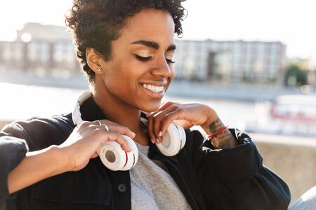 Portrait closeup of happy african american woman with curly afro hairstyle using headphones while sitting on bench near riverfront