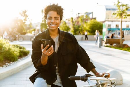 Photo of charming african american woman wearing casual clothes smiling and holding cellphone while sitting on bicycle in city park