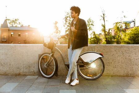 Photo of young african american woman wearing casual clothes standing with bicycle and using earphones while walking along riverfront