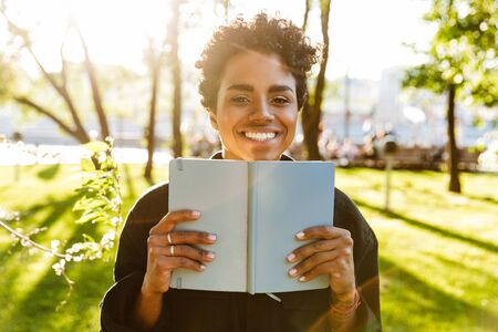 Photo of adorable african american woman with curly hair smiling and holding day planner while walking in city park