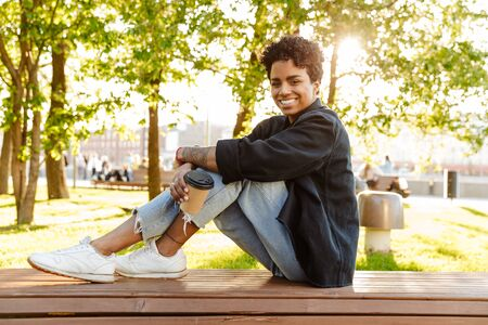 Photo of cheerful african american woman with curly hair holding paper cup while sitting on bench in city park 版權商用圖片