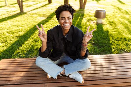Photo of cute african american woman with curly hair showing peace sing and smiling while sitting on bench in city park 版權商用圖片