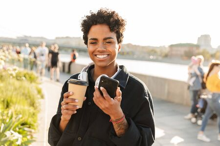 Portrait of nice african american woman with curly afro hairstyle holding smartphone while walking along riverfront 版權商用圖片