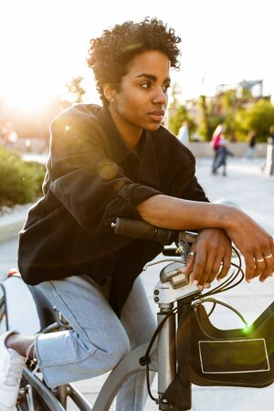 Photo of serious african american woman wearing casual clothes looking aside while sitting on bicycle in city park 版權商用圖片