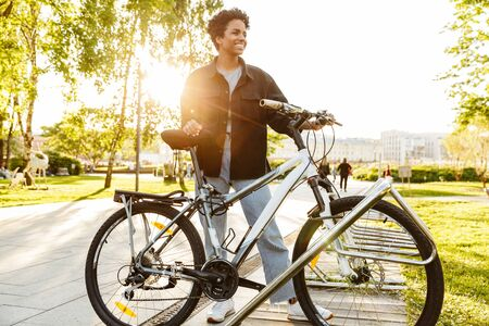 Photo of beautiful african american woman wearing casual clothes standing with bicycle while walking in city park